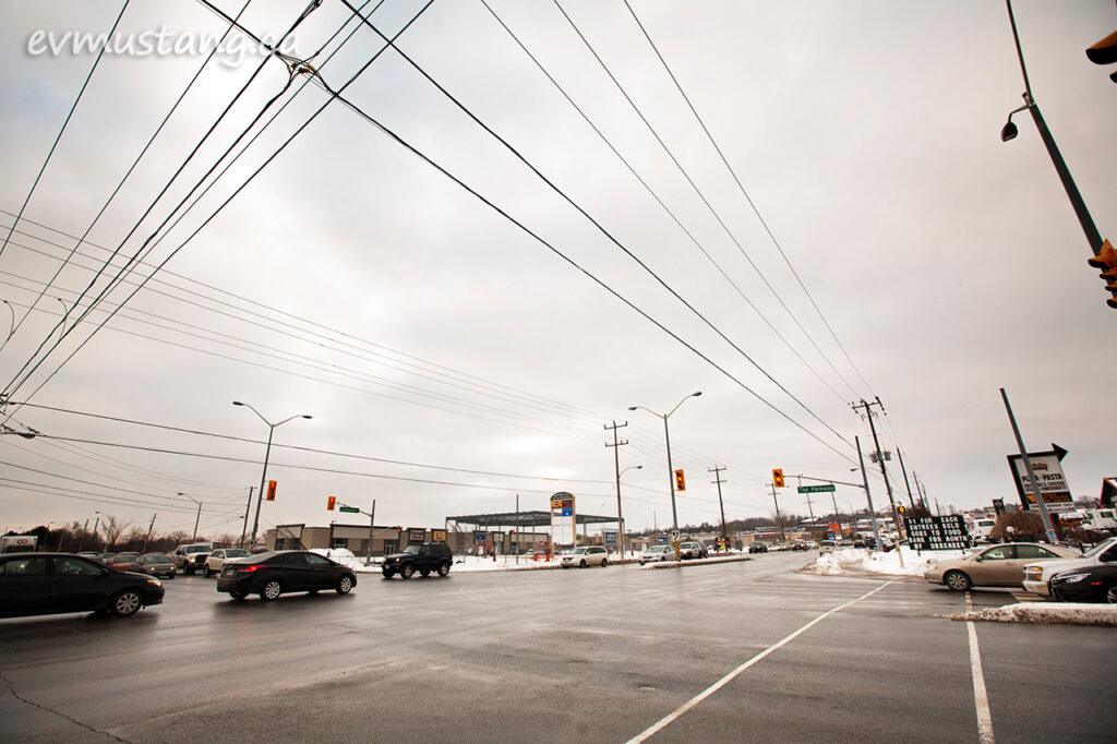 image of the intersection of lansdowne and the parkway in peterborough, ontario on a cloudy day three days before christmas showing overhead wires and stop lights and the pedestrian walkway