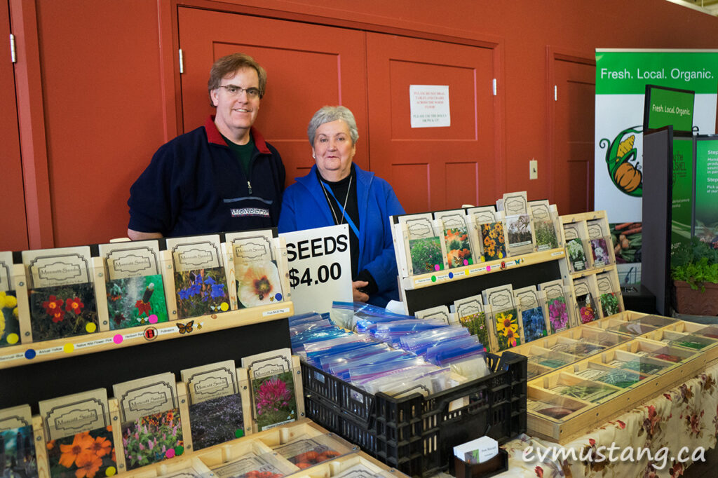 image of the owners of muscott seeds standing behind their booth at peterborough's seedy sunday seed exchange
