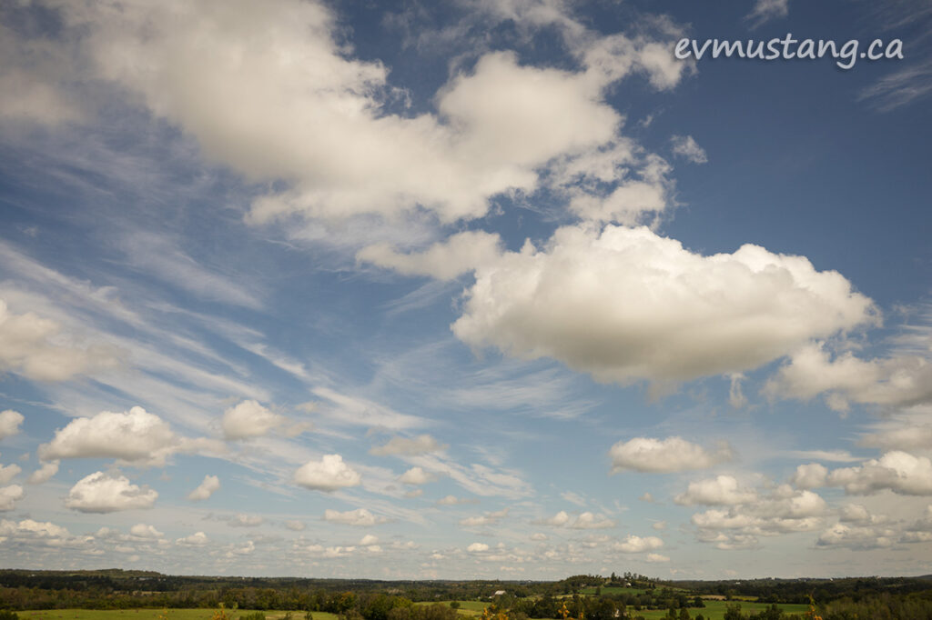 image of distant late summer country side under puffy clouds from the top of the first hill of the harold town trails