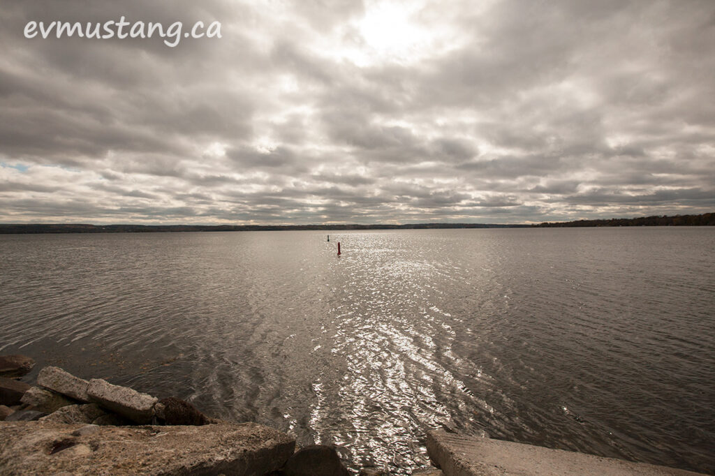 image of buoys in rice lake with a patch of sun breaking through the clouds creating reflections on the water with large shore rocks in the foreground