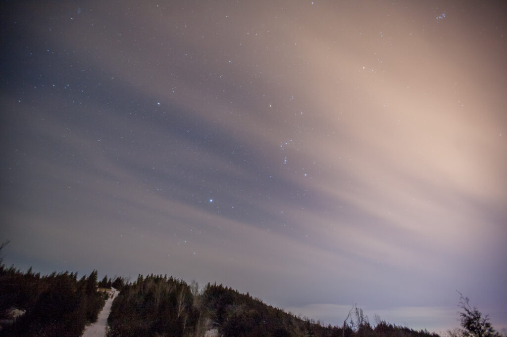 image of the starts in a winter sky with gauzy clouds