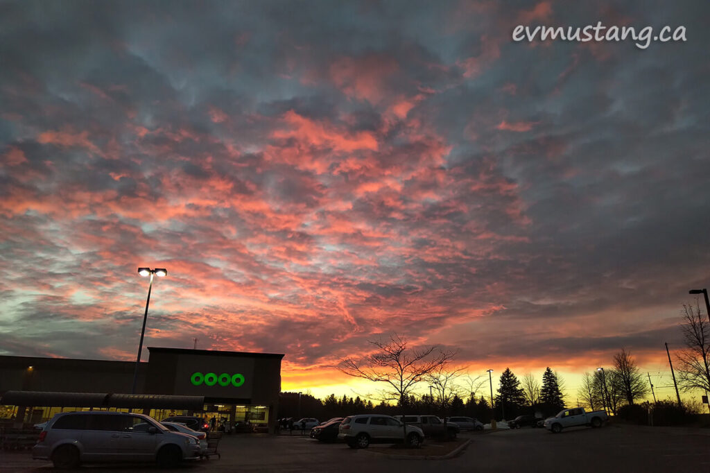 image of intense peach and plum sunset over suburban grocery store