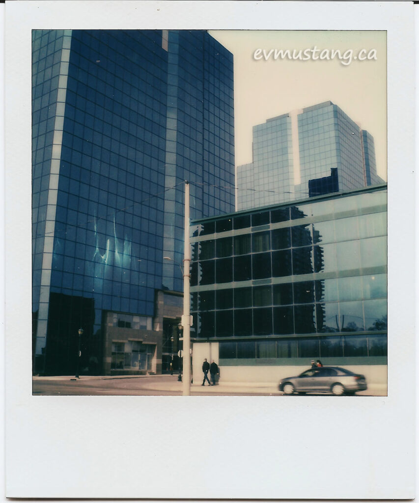 scan of a polaroid of a series of glass and steel buildings reflected in each other with pedestrians and a car passing on the sidewalk below