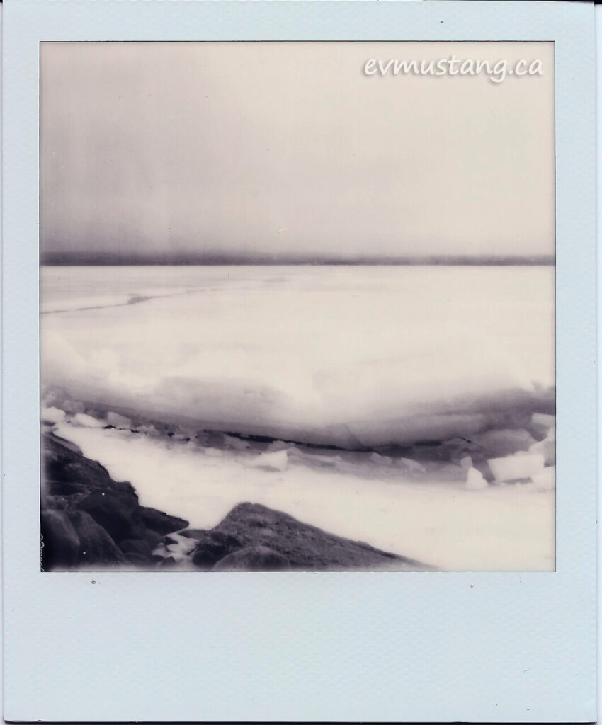 scan of a black and white polaroid of large sheets of ice bucked up against rocks