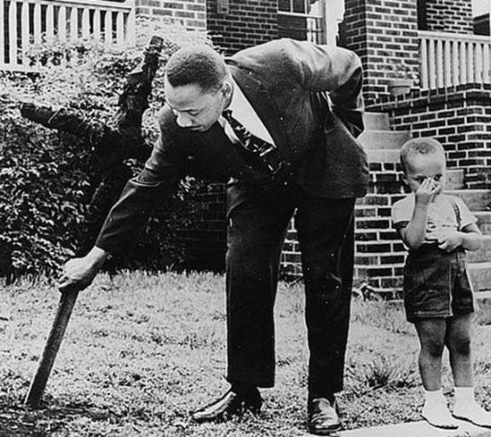 Martin Luther King tar bort et utbrent kors fra hagen  sammen med sin sønn, 1960