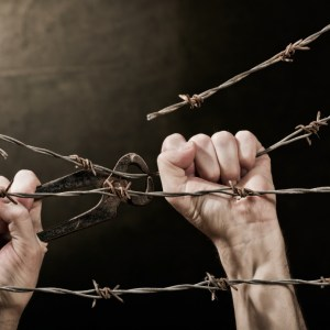 old rusty barbed wire with hand on the dark background