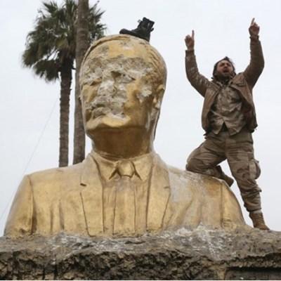 أحد الثوار يعتلي تمثالاً للرئيس السوري السابق حافظ الأسد في إدلب - وكالات