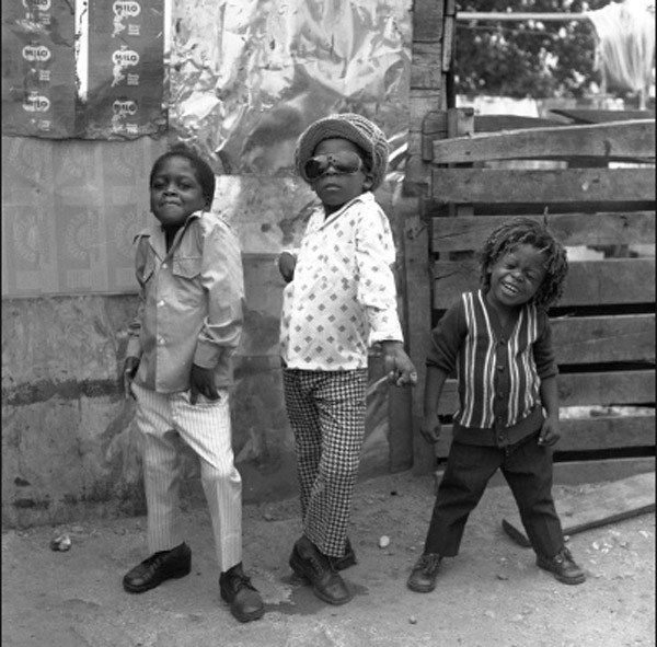 Three boys pose for a camera on the streets of Jamaica.