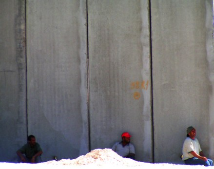 three people by the wall near the Qalandiya Ch...