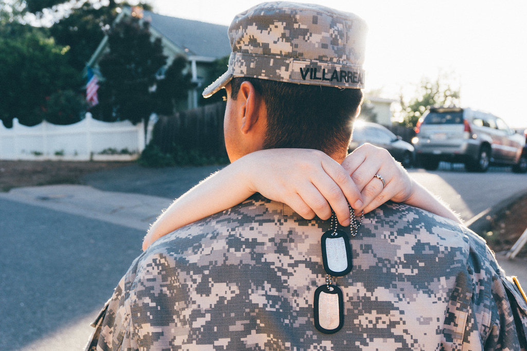 Imagen gratis de una chica abrazando a un militar de espaldas