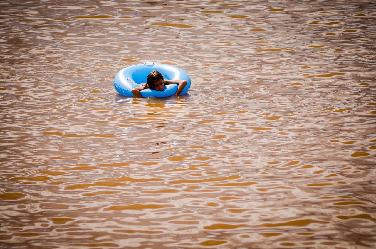 Una niña flota con su salvavidas de juguete en las aguas bajas del río Paraná, en la Playa San José de Encarnación. (Elton Núñez)