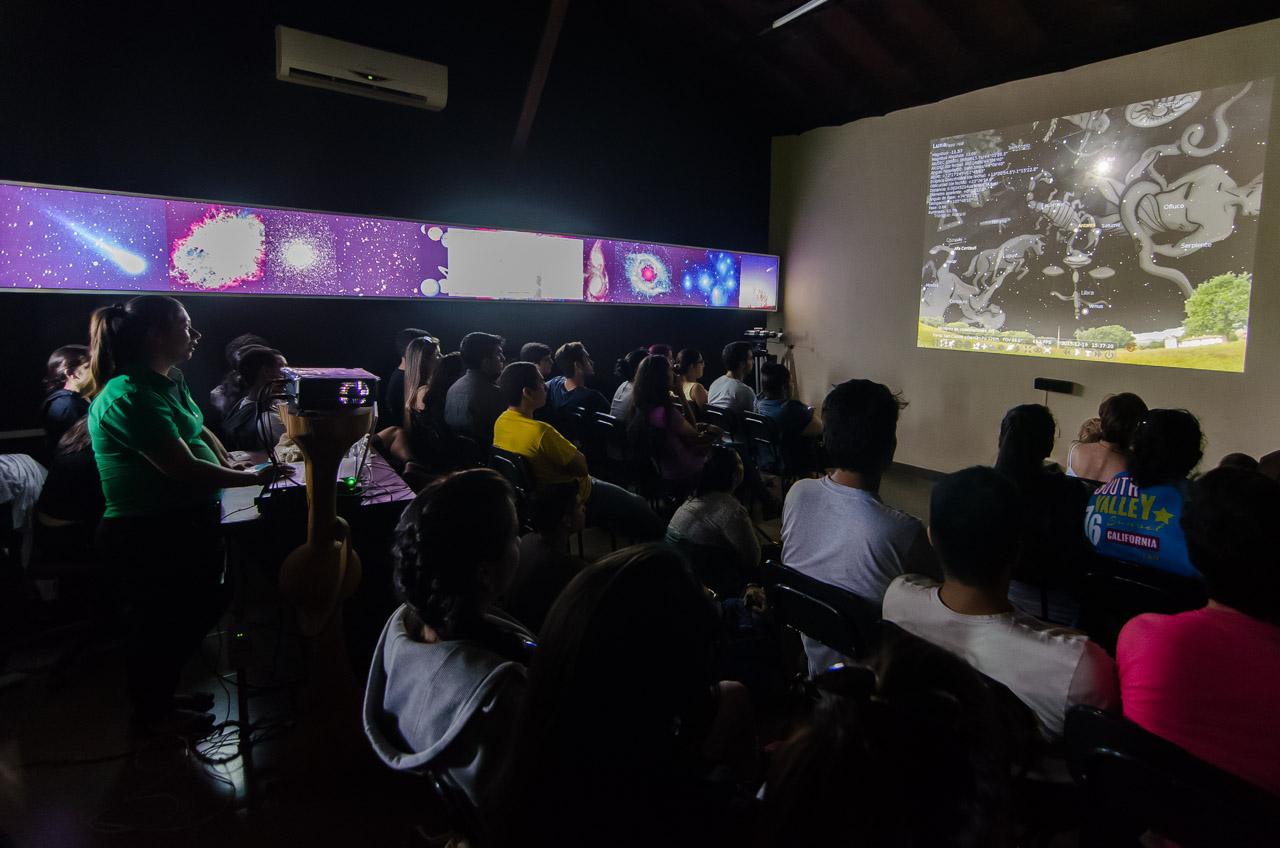 Una funcionaria del Museo Astronómico de San Cosme y Damián proyecta unas imágenes para explicar a los presentes todo lo referente a las constelaciones que pueden verse en las distintas estaciones del año, desde Paraguay, específicamente desde el Centro Astronómico. (Elton Núñez)