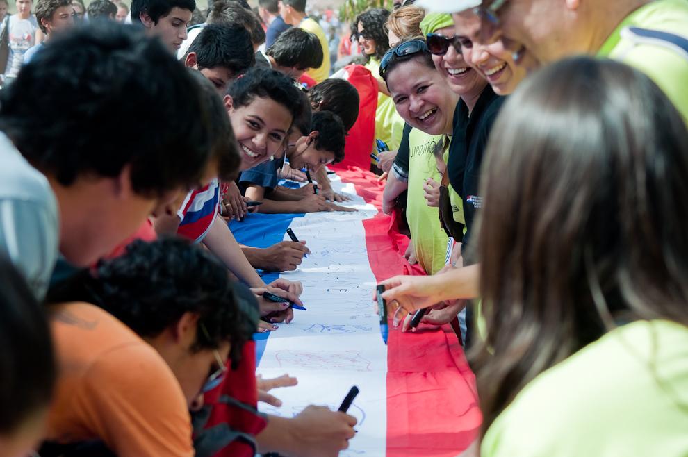 Una bandera de unos veinte kilómetros de extensión, hecha con segmentos de banderas confeccionadas en diferentes instituciones educativas de la patria, era firmada por la gente mientras se iba uniendo. (Elton Núñez - Asunción, Paraguay)
