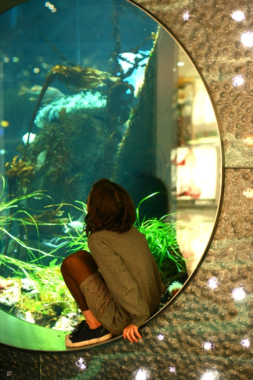 Girl sits in front of aquarium in YVR airport