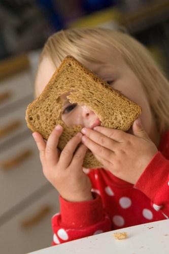 toddler peeking through a hole in whole-grain bread