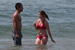 Young healthy couple in swimsuits wade in the water reflecting the picture of perfect health and fitness and youth. Beach scenes from Morro Strand State Beach