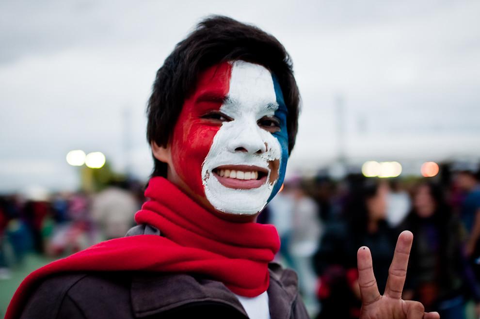 Un joven se pinta el rostro con los colores de la bandera paraguaya durante el Festival de Globos Aerostáticos en la explanada del Palacio de López el domingo 15 de Mayo. (Elton Núñez - Asunción, Paraguay)