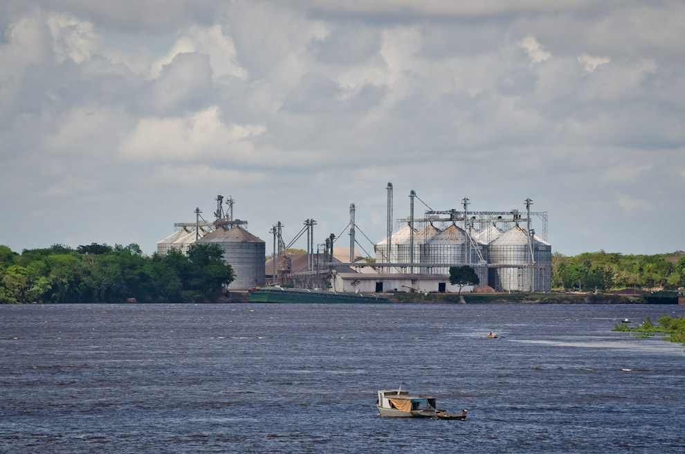 Silos de grano pueden verse a lo lejos mientras una pequeña embarcación navega por las aguas del río Paraguay en el puerto Antequera de San Pedro de Ycuamandiyú. (Elton Núñez)