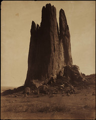 [No. 1007. View of a sandstone rock formation identified as the Tower of Babel, the Garden of the Gods, Colorado Springs (El Paso County), Colorado. A man stands near the base of the outcrop. Shows a flat grassy plain, large boulders and brush].