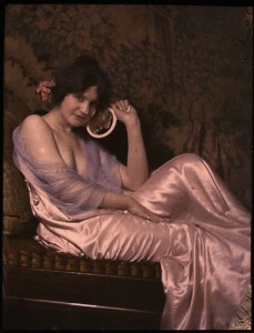 Woman in satin dress holding mirror