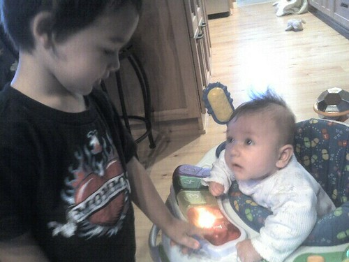 Mason showing Jude how to use a toy