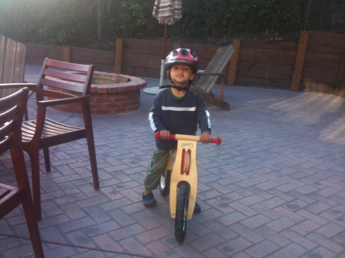 Mason on his new skuut on our patio