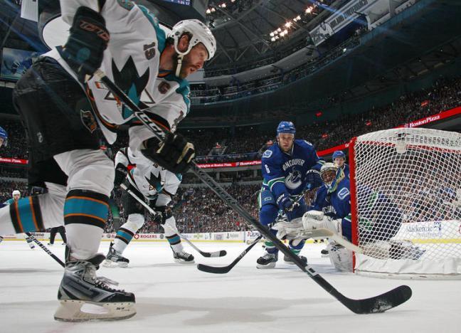 Sami Salo attempts to stop the Sharks' Joe Thornton.