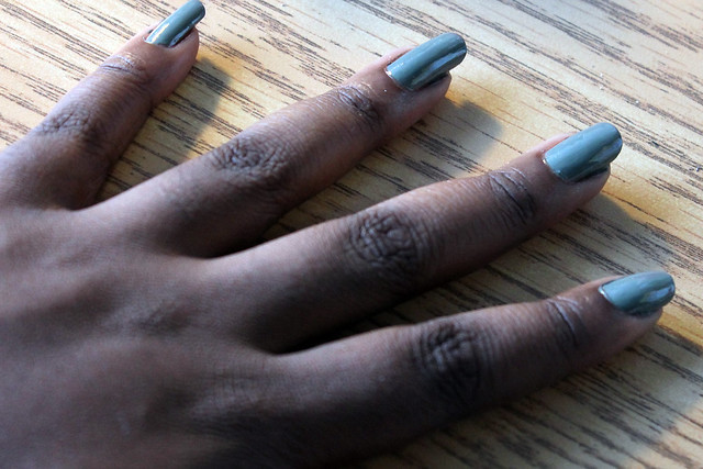 hand with fingers splayed, nails painted green nail