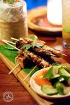 A selection of skewers from the menu is served on a platter with house pickles and steamed coconut rice in a bamboo basket.