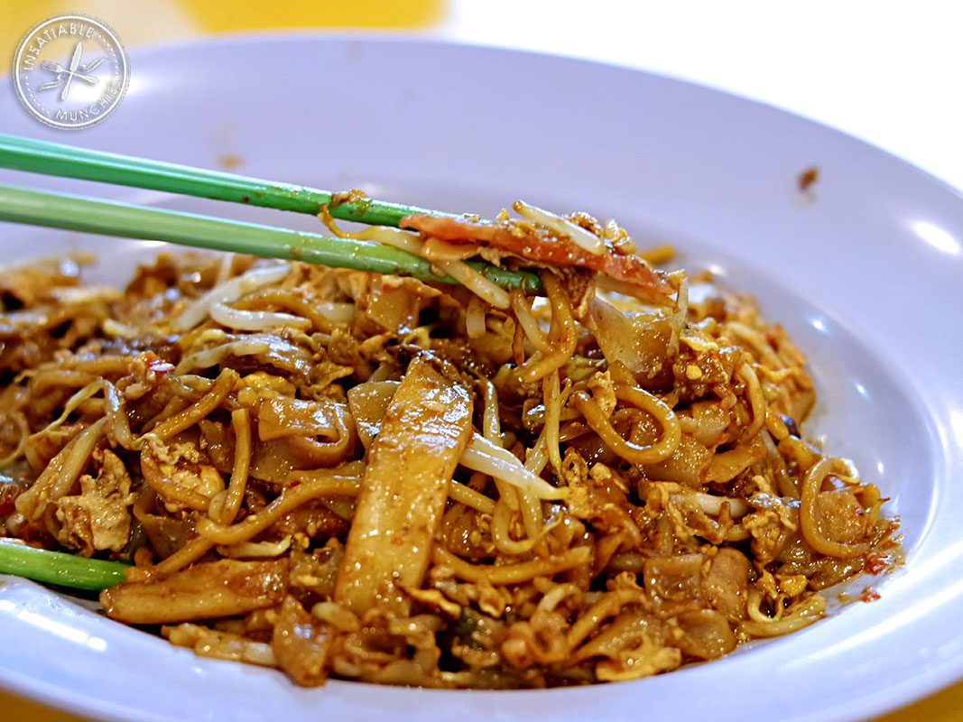 A mixture of rice and egg noodles are fried in soy based sauces, with pieces of fish cake, fresh cockles and chilli.