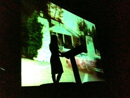 A silhouette of screenwriter Jenny Lumet, with a Jonathan Demme montage playing in the background