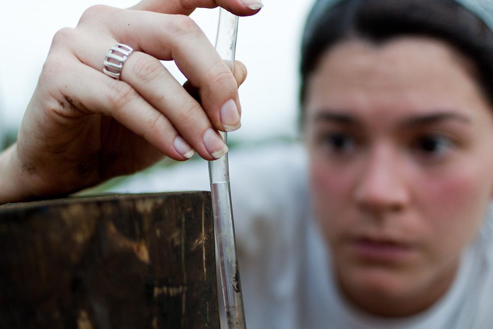 Una voluntaria utiliza una manguera con agua para medir el nivel de la colocación de los pilotes de madera como cimiento de la construcción de una casa en la primera etapa del sábado que corresponde principalmente a la instalación de los cimientos y el piso. (Elton Núñez - Asunción, Paraguay)