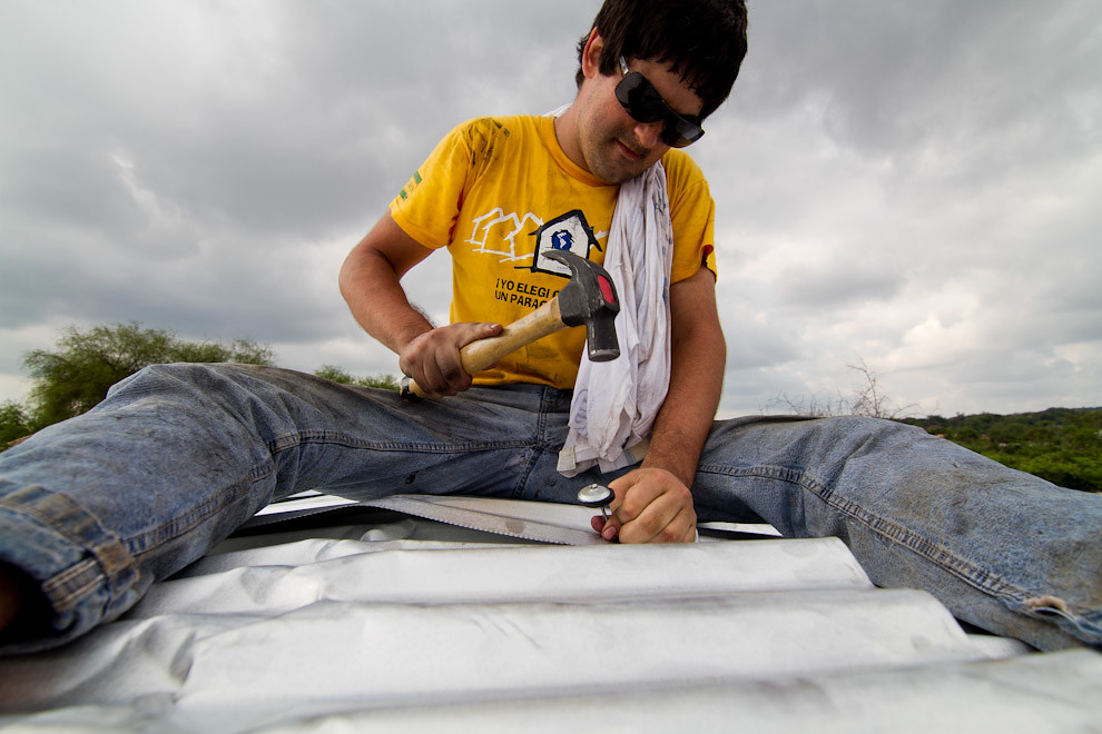 Sobre el techo un voluntario clava las últimas chapas de Zinc contra las vigas de madera. (Tetsu Espósito - Lambaré, Paraguay)