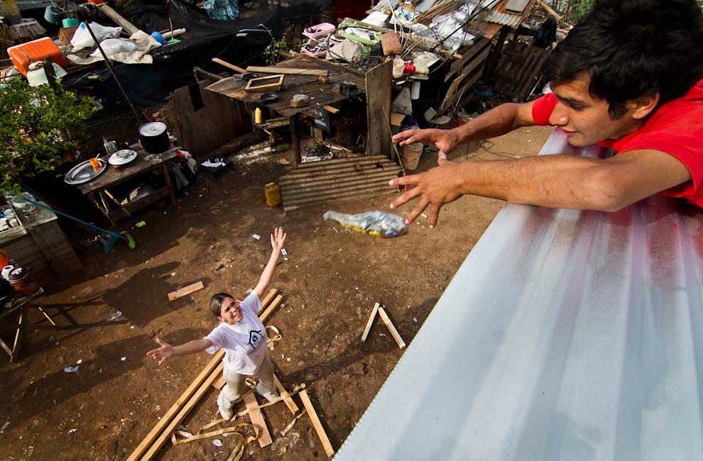 Una voluntaria lanza los clavos necesarios para fijar las chapas a su compañero que se encuentra trabajando en el techo de la vivienda. (Tetsu Espósito - Lambaré, Paraguay)