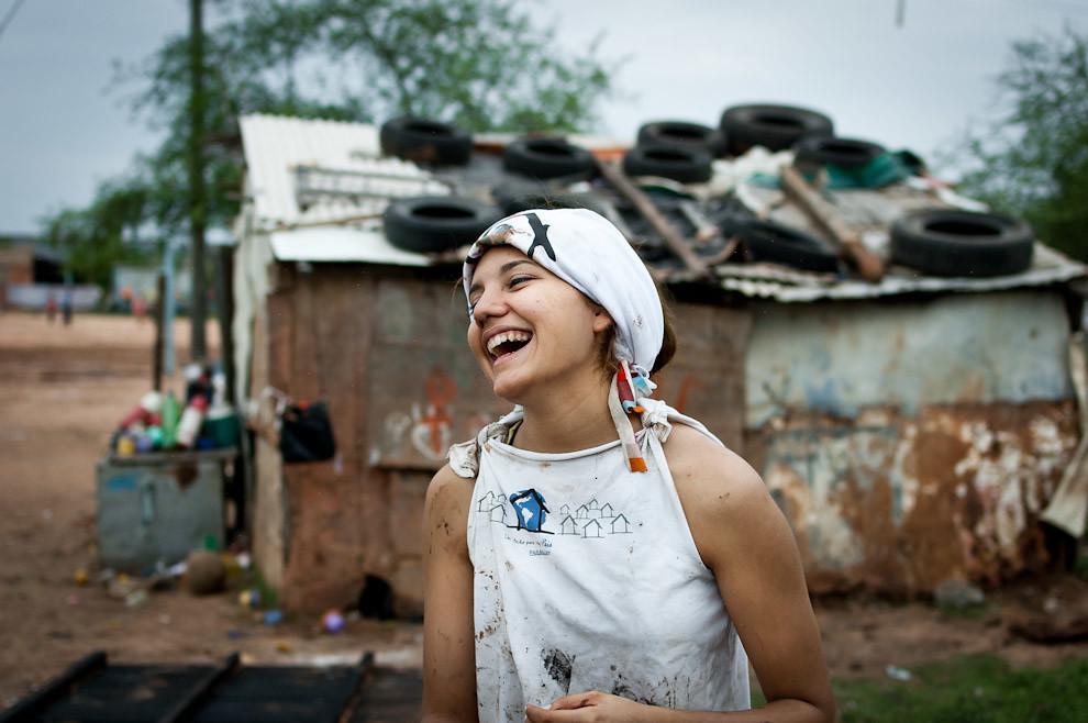 Una voluntaria sonrie con sus compañeros techeros durante una ronda de juegos de adivinanzas para amenizar la tarde de construcción de cimientos. (Elton Núñez - Asunción, Paraguay)