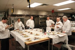 Judges grade plates at the Art Institute's black box cooking competition