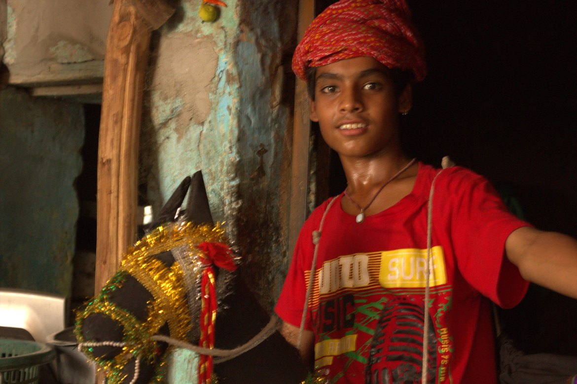 A young boy performs Kachchi Ghodi during the Kathputli Colony slum visit