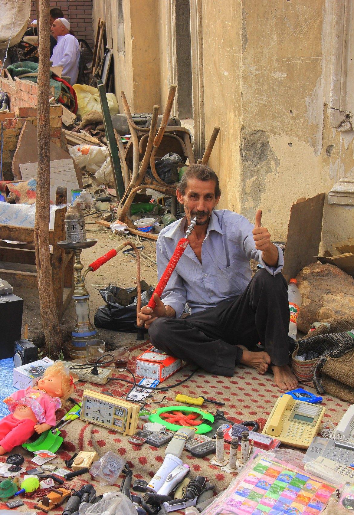 Junk seller smoking shisha at souq al goma