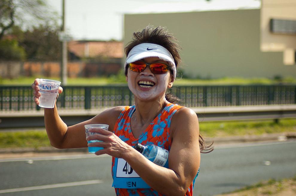 Una atleta toma agua durante su carrera en el Maratón del Bicentenario en la categoría de 48 kilómetros. (Elton Núñez - Asunción, Paraguay)