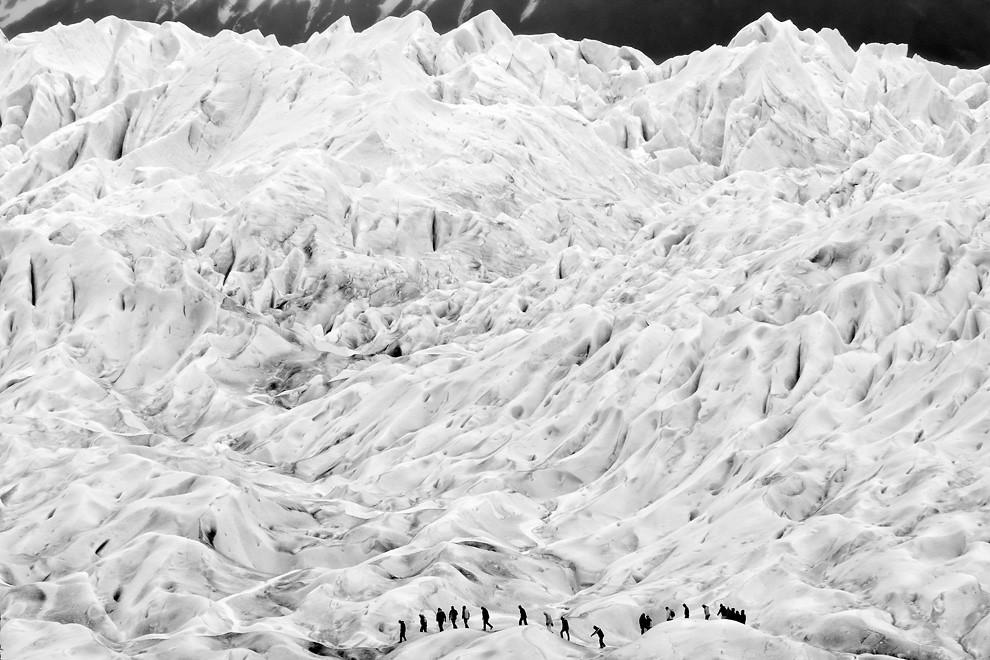 El blanco majestuoso del glaciar contrasta a las siluetas humanas. Cientos de turistas  acuden diariamente a la caminata sobre el Perito Moreno. (Guillermo Morales -  Patagonia, Argentina)