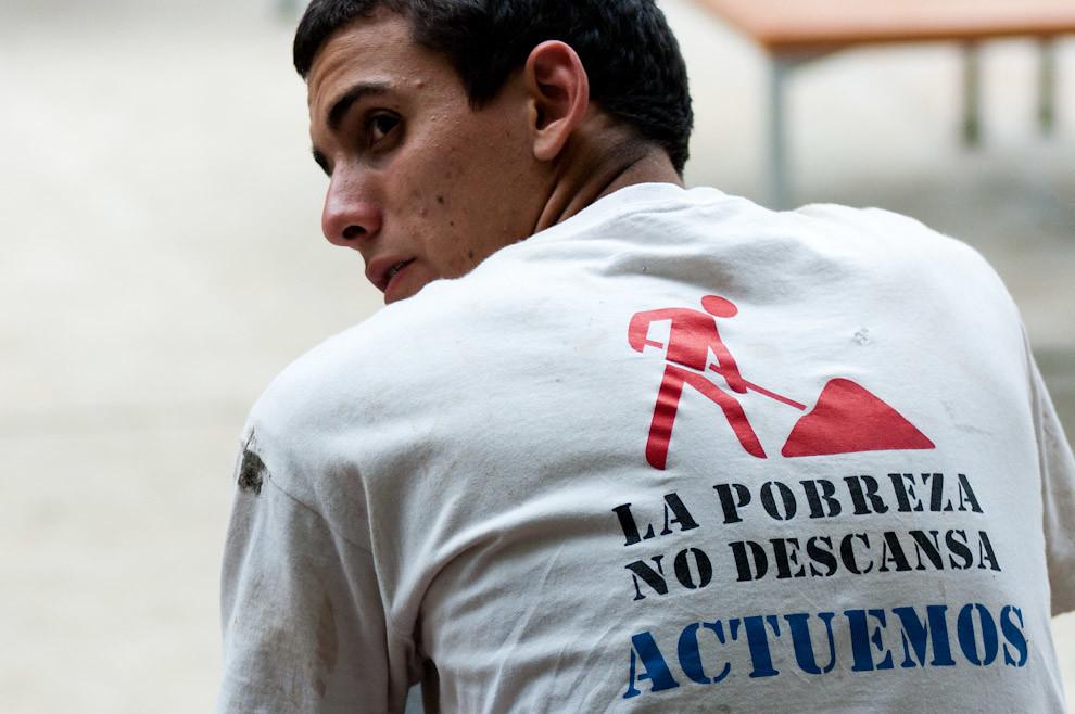 """Un muchacho voluntario de la campaña """"Un techo para mi País"""" espera sentado a sus compañeros antes de salir a hacer las construcciones un sábado de Setiembre en la zona del bañado Yukyty. (Elton Núñez - Asunción, Paraguay)"""