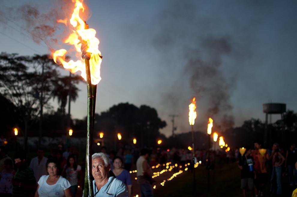 Un encargado se ocupa de encender las antorchas alineadas a minutos de comenzar la marcha tradicional de Tañarandy del Viernes Santo. (Elton Núñez - San Ignacio, Paraguay)