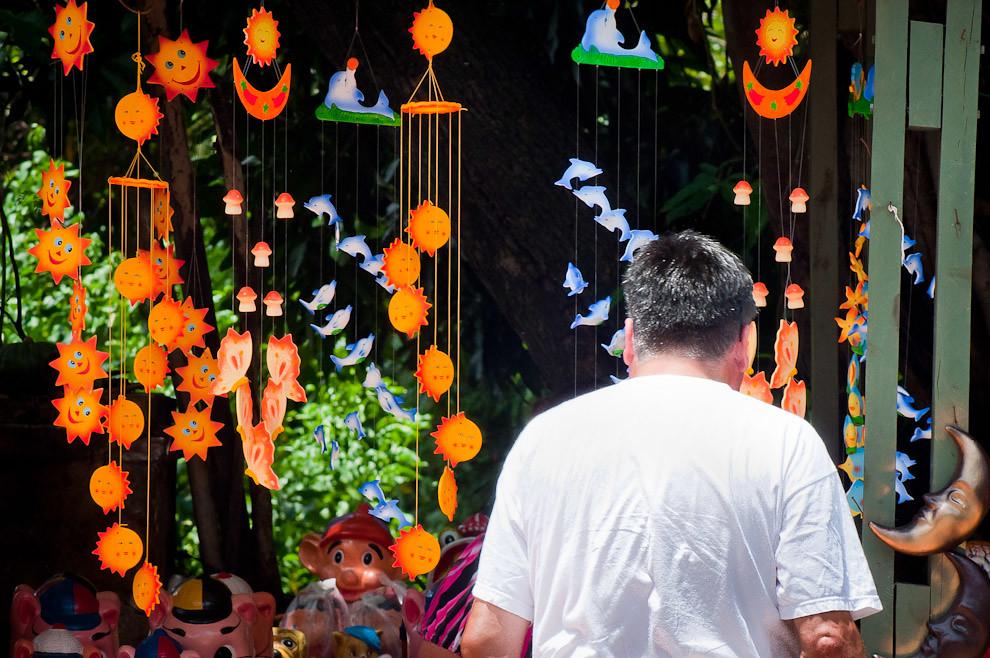 Un comprador selecciona artesanías para llevar a su casa en la Avda principal La Candelaria de Areguá en el día siguiente de la Noche Buena. (Elton Núñez - Areguá, Paraguay)
