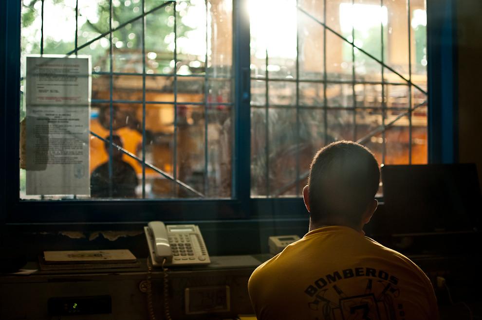 Un voluntario operador de radio comienza su jornada encendiendo su computadora. Bien temprano en la mañana los turnos de los operadores de radio se cambian, también el resto del personal que debe volver a sus casas, al trabajo, a la facultad, a sus respectivas vidas particulares. Los bomberos ingresantes repiten las mismas rutinas de supervisión de los vehículos, equipos y herramientas tal como lo hizo la guardia anterior, con el objetivo de asegurar que todo esté en orden, en su lugar; y que  nada falte para comenzar un nuevo ciclo en el día. (Elton Núñez).