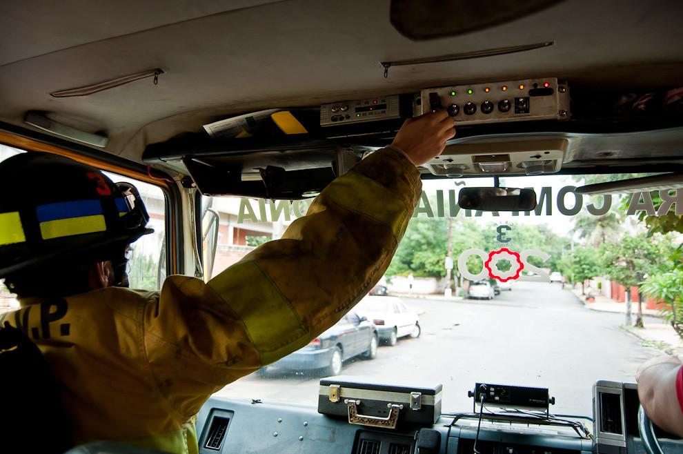Un tripulante del móvil AB-33 acciona el botón que hace sonar la sirena rotativa que alerta a los transeúntes de la urgencia con que viajan. Por parte de la ciudadanía se espera que al oír la sirena despejen el camino por un breve momento. Sólo hay que recordar que detrás de un móvil dirigiéndose con urgencia hay una persona indefensa aguardando su socorro. (Elton Núñez).