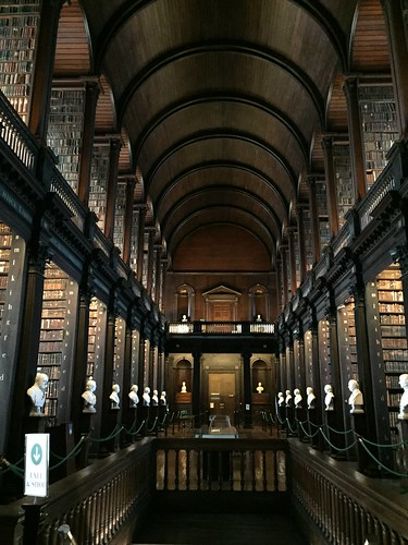 The long room trinity college Dublin as seen from its main entrance. As you step inside, you are surrounded by arcades covered in books under dark, vaulted celings