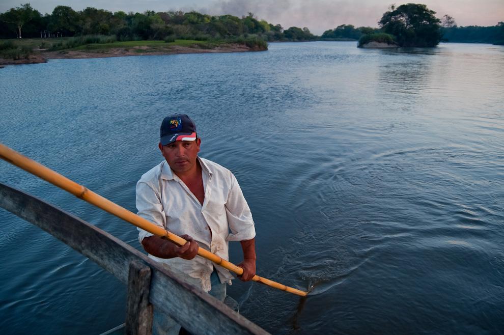Un canoero ofrece su servicio de traslado en una improvisada balsa hecha con una plataforma de madera sostenidas por dos canoas, este señor traslada a la gente de un lugar a otro del Río Pirapó sin cobrar tarifa alguna más que a voluntad. (Elton Núñez)