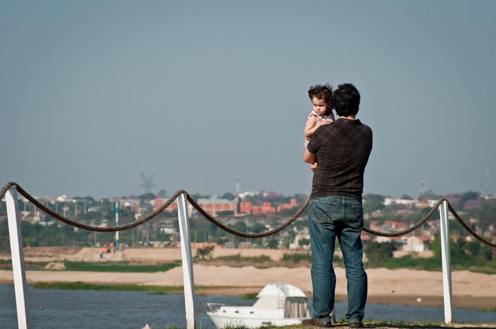 Una niña observa a su alrededor mientras el padre contempla la bahía de Asunción, en la tarde del lunes 15 de Agosto en el Parque Litoral. (Elton Núñez)