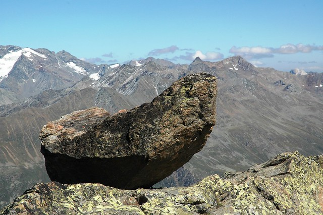 Hiking in Oetztal: Large rock, at above 3000 metres altitude, between snow-capped mountains in Oetztal, in the Austrian region of Tyrol.