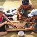 Loi Assistant Kaulana Vares, of the University of Hawaii at Manoa's Ka Papa Loi O Kanewai, teaches youngsters to pound taro at the University of Hawaii exhibit at the Smithsonian Folklife Festival.